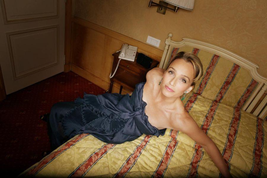 L'actrice, en robe du soir Yves Saint Laurent Rive Gauche, pose sur le lit de sa chambre à l'hôtel Majestic à Cannes.