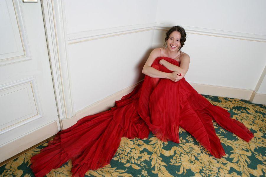 L'actrice belge est en robe de soirée rouge Elie Saab, assise par terre dans une chambre de l'hôtel Carlton, lors du Festival de Cannes 2006.