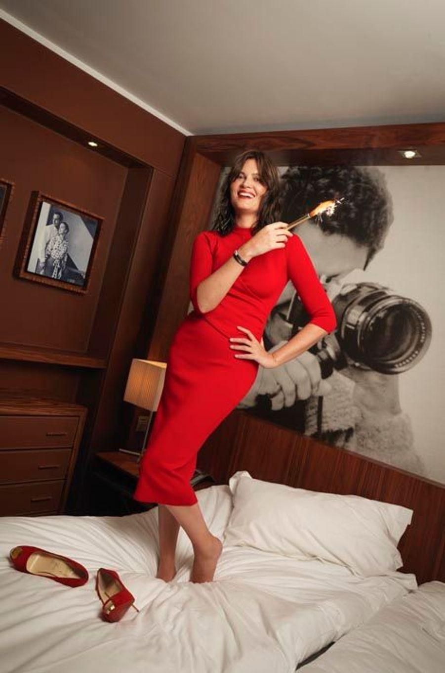 Marina Hands pose en robe rouge Dior, pieds nus debout sur un lit.