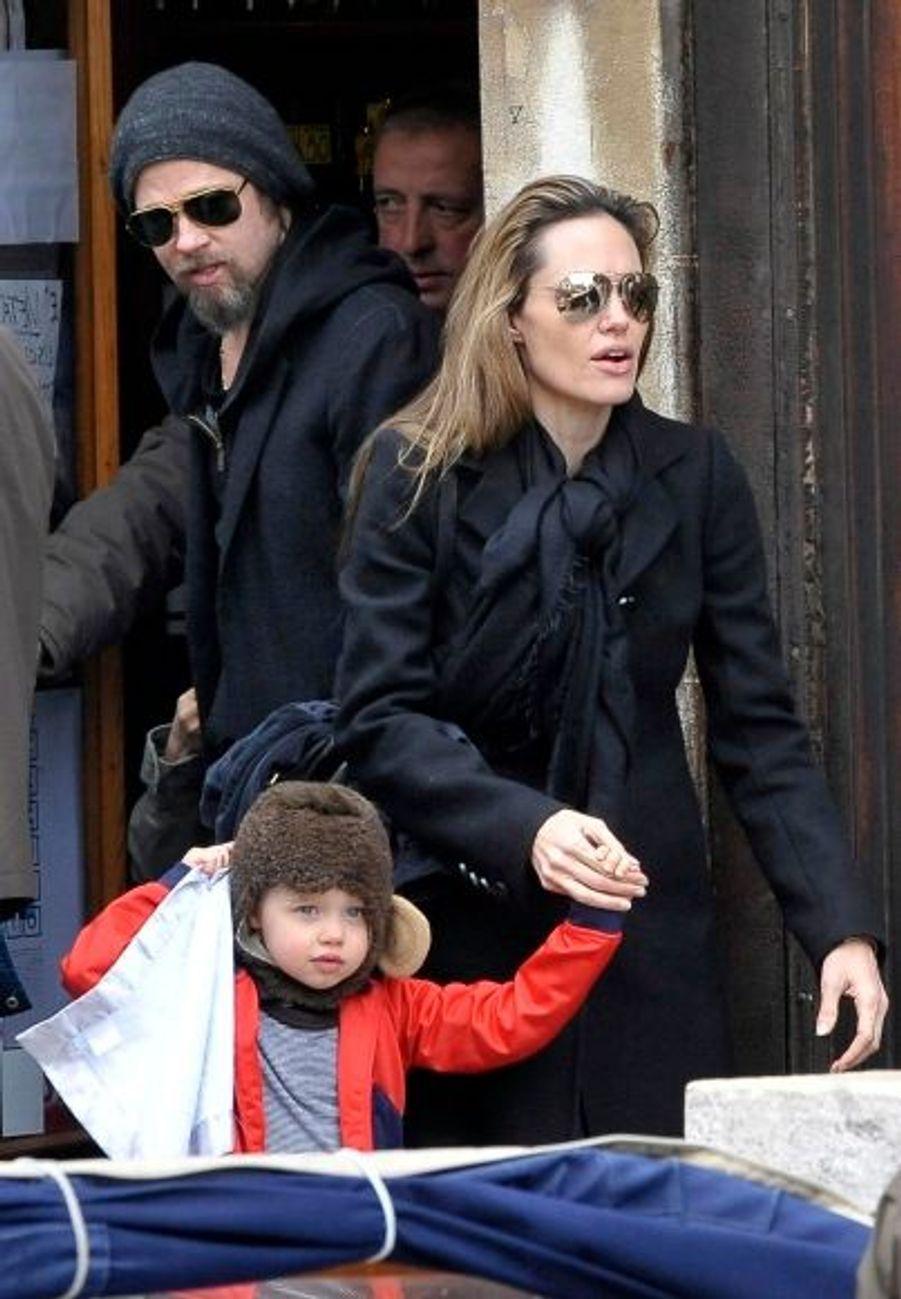 Angie tient la main de la petite Shiloh, suivie de Brad, avec Maddox.