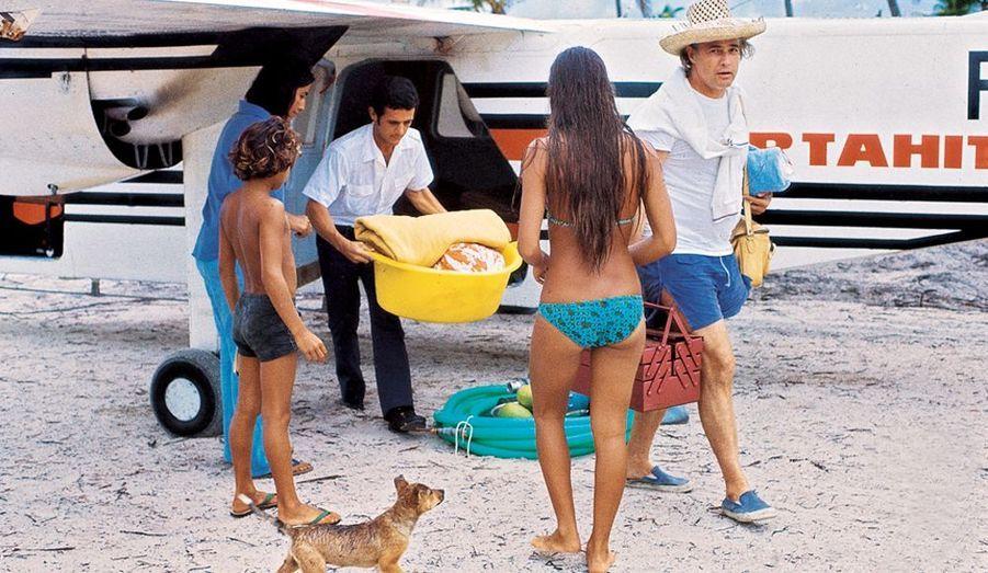 1971, Marlon débarque du Twin Otter qui vient de Papeete en quatorze minutes. Son fils Simon l'accueille, avec Dora, la femme de l'architecte, et Moya, de dos.