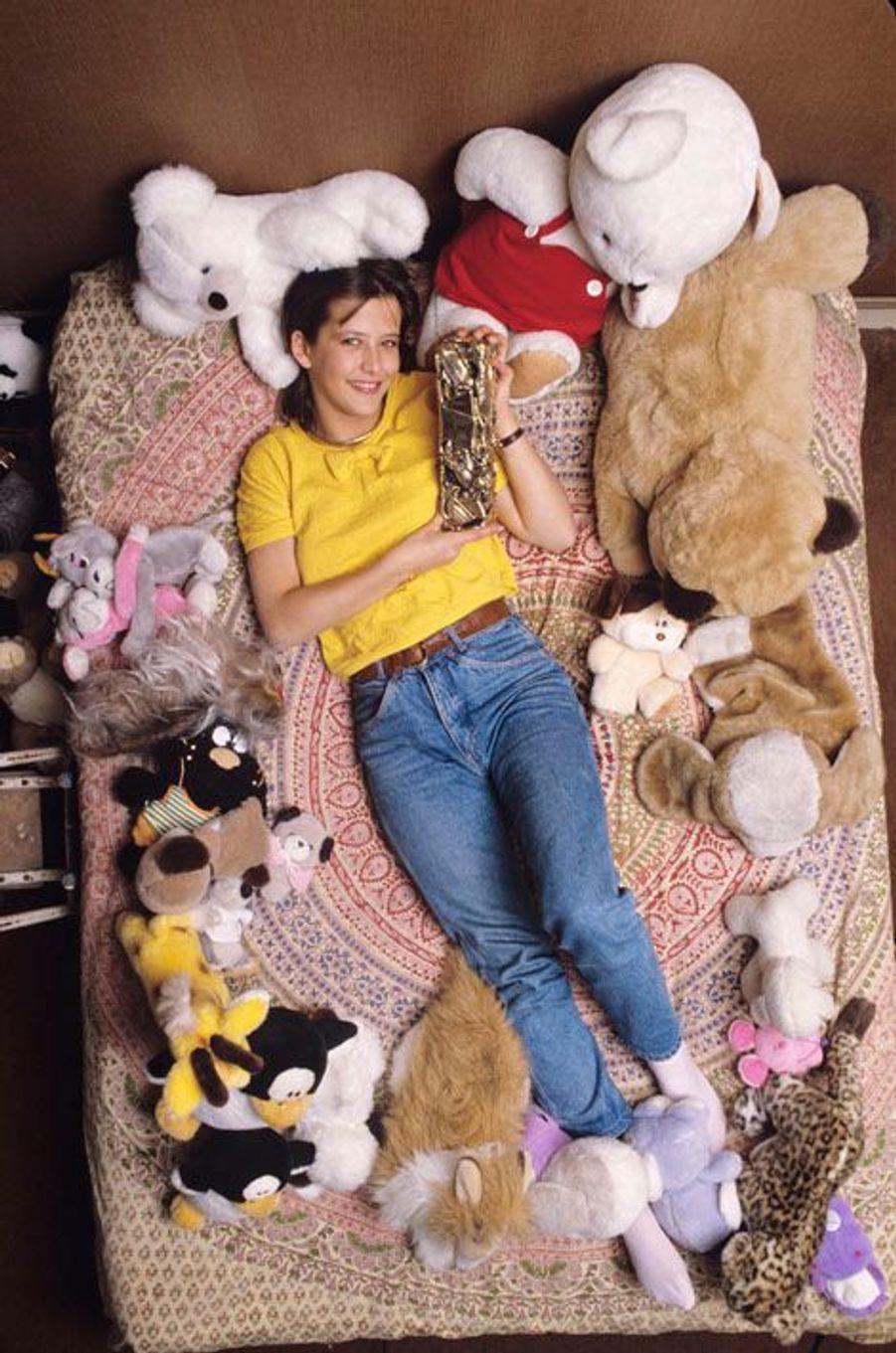 """Sceaux (92), mars 1983 : Sophie Marceau, 16 ans, chez ses parents : souriante, allongée sur son lit au milieu des peluches, posant avec le César du meilleur jeune espoir féminin 1983, décerné pour le film """"La boum 2""""."""