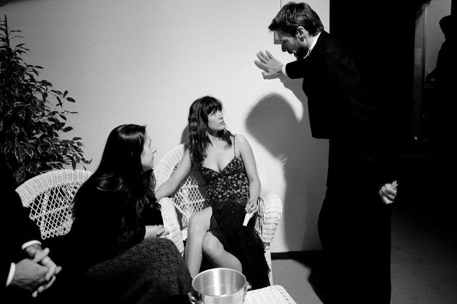 Le 52ème Festival de Cannes se déroule du 12 au 23 mai 1999 : Lambert Wilson barbu, de profil, debout discutant avec Sophie Marceau en robe-fourreau Ungaro, assise en coulisses en présence d'une femme non identifiée.