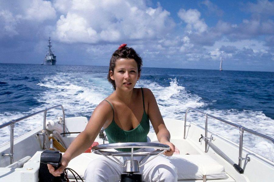 """En vacances après le tournage du film """"Mes nuits sont plus belles que vos jours"""" de Andrzej Zulawski, l'actrice Sophie Marceau assise à la barre d'un bateau voguant sur l'océan"""