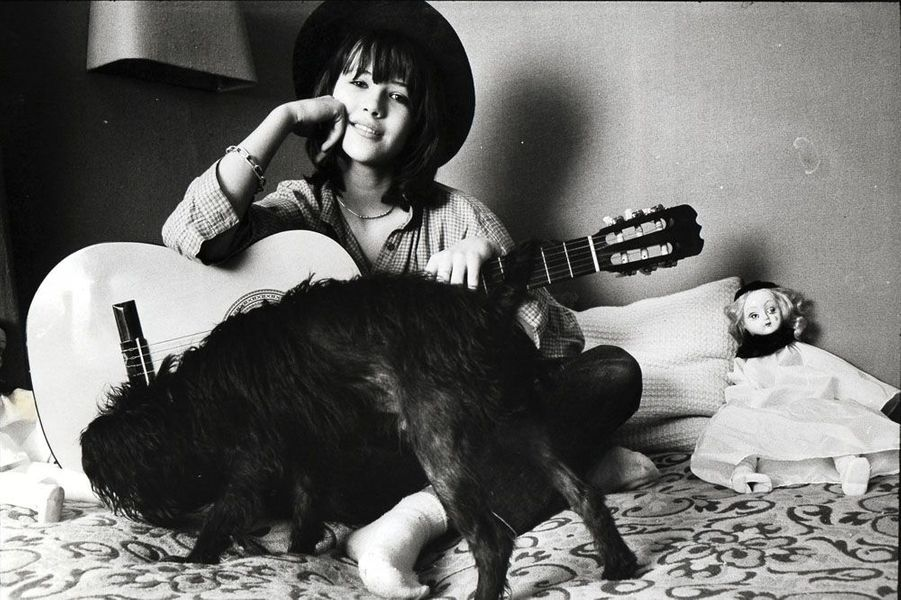 Attitude souriante de Sophie Marceau coiffée d'un chapeau, assise en tailleur sur son lit, entourée de sa guitare, de son chien Rubens un schnauzer nain et d'une poupée chez ses parents à Gentilly.