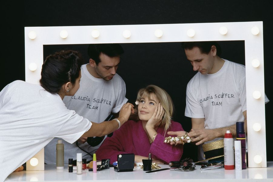 Claudia Schiffer se fait maquiller lors d'un shooting à Paris en 1990