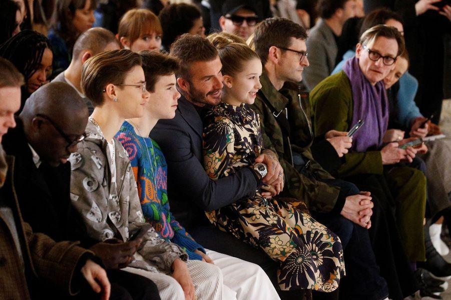 David Beckham assis avec ses enfants Romeo, Cruz, et Harper (l'aîné Brooklyn est absent), pour assister au défilé de sa femme Victoria à la Fashion Week de Londres le 16 février 2020.