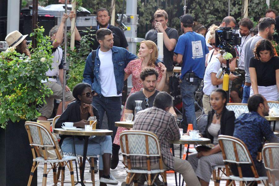 Sebastian Stan, Jessica Chastain et Edgar Ramirez (assis au milieu des tables) sur le tournage du film «355» à Paris le 11 juillet 2019