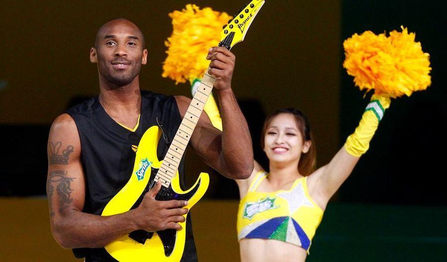 Le basketteur américainKobe Bryant pose avec une guitare électrique lors d'un match de basket-ball caritatif à Shanghai.