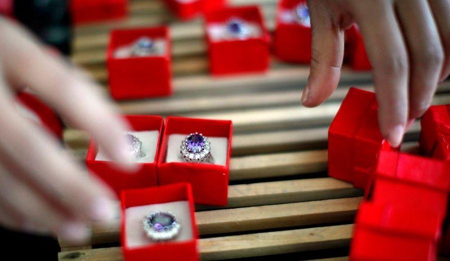 Une employée d'une usine de bijoux de Yiwu (Chine), dispose des répliques de la bague de fiançailles de Kate Middleton dans leur écrin. Depuis l'annonce, les fabricants chinois tirent profit de l'engouement autour du mariage princier.