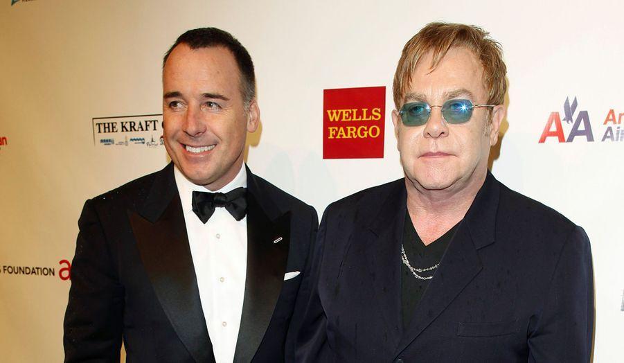 """Elton John et son compagnon David Furnish posent sur le tapis rouge juste avant le gala de charité """"An Enduring Vision 2012"""", organisée par la fondation du chanteur à New York."""
