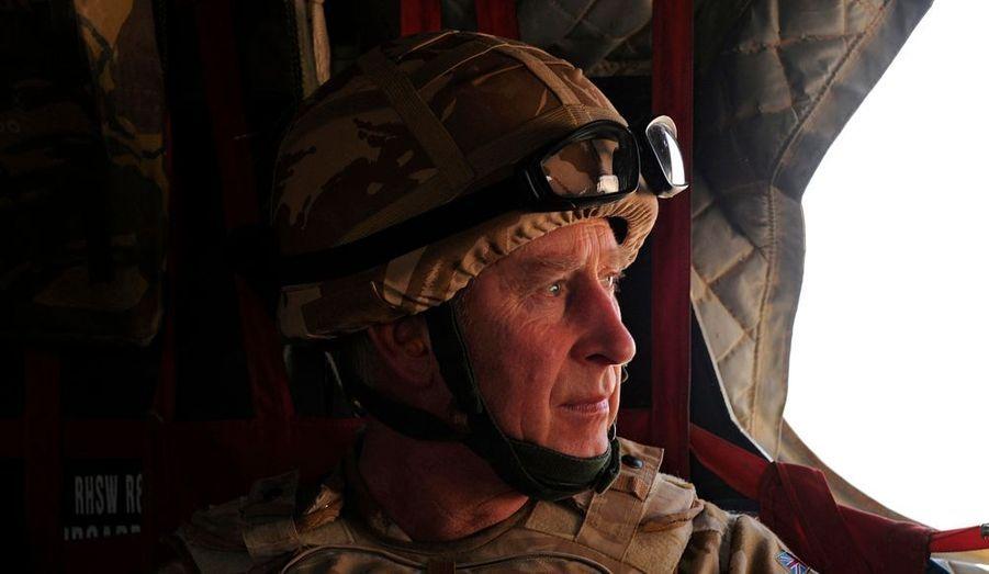 Le prince Charles regarde par la fenêtre d'un hélicoptère militaire britannique lors de son trajet pour Lashkar Gah en Afghanistan. Le père de William et Harry, tous deux militaires ayant servi sur les terres afghanes, est arrivé dans le pays pour une visite surprise. Il a notamment rencontré des soldats britanniques en poste dans la province de Helmand, une zone de combats intenses située au sud du pays.