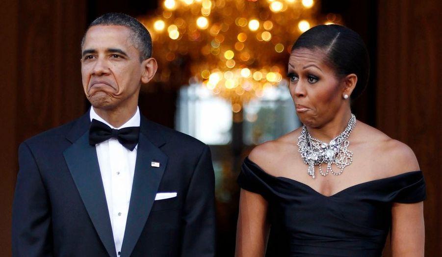 En visite officielle en Grande-Bretagne, Barack Obama et la Première dame américaine Michelle Obama réagissent à l'arrivée de la voiture de la Reine Elizabeth II à Winfield House, à Londres.