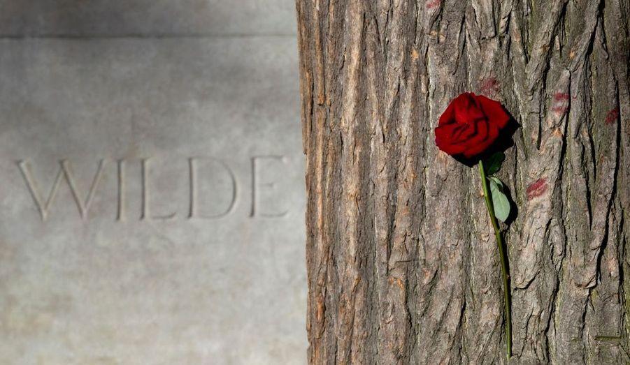 """La tombe rénovée d'Oscar Wilde a été dévoilée aujourd'hui au cimetière du Père Lachaise. La pierre de la dernière demeure de l'écrivain irlandais était recouverte depuis des années des baisers de ses admirateurs. Si le geste était joli, le rouge à lèvre, mais également l'encre des messages adressés à l'auteur, était devenu un problème pour la pierre. La tombe de Wilde, mort en1900 à Paris, a donc été nettoyée et une plaque de verre a été installée pour prévenir les nouveaux gestes d'affections destinés à l'auteur du """"Portrait de Dorian Gray"""" et de """"L'importance d'être Constant""""."""