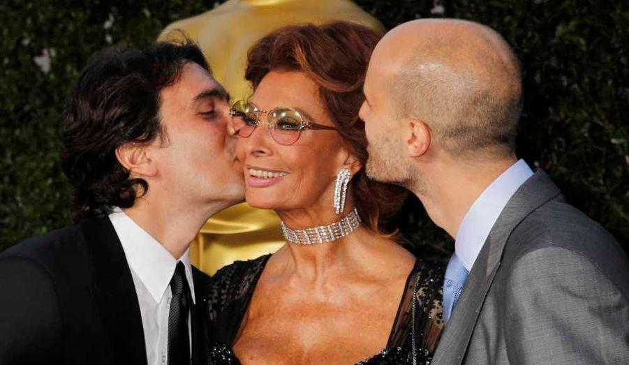 L'actrice italienne Sophia Loren entourée de ses fils, le compositeur Carlo Ponti (à G) et le réalisateur Edoardo Ponti, à leur arrivée à l'Academy of Motion Picture Arts & Sciences pour un hommage à la star.