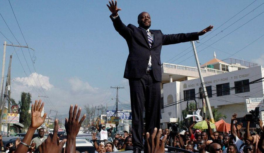 Le rappeur Wyclef Jean monte sur le toit de sa voiture pour saluer la foule après avoir officiellement annoncé sa candidature à la présidence de Haïti dans le quartier de Delmas à Port-au-prince, hier. Les élections auront lieu au mois de novembre prochain.