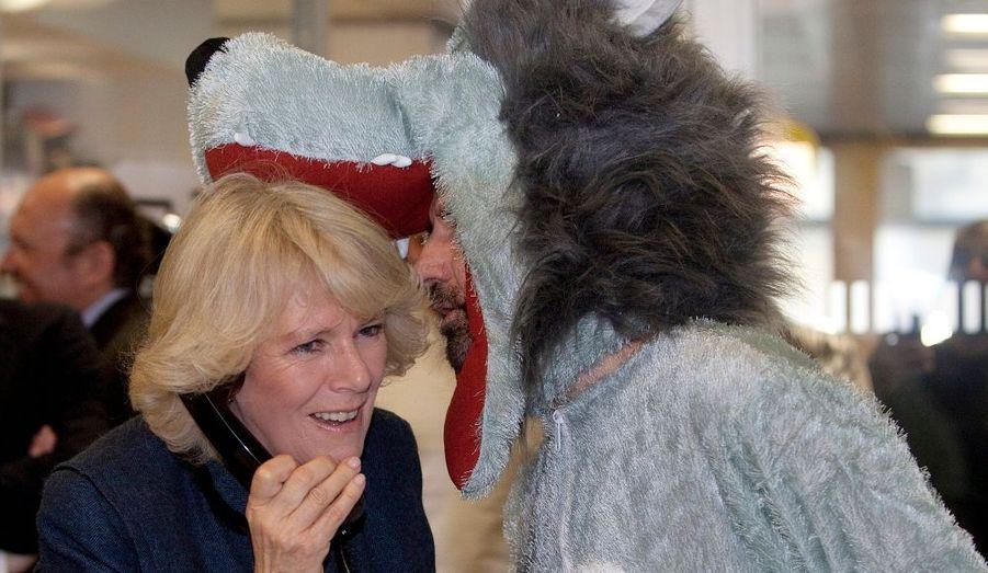 La duchesse de Cornouailles, aidée d'un courtier déguisé, donne des coups de téléphone pour lever des fonds lors d'une œuvre de charité.