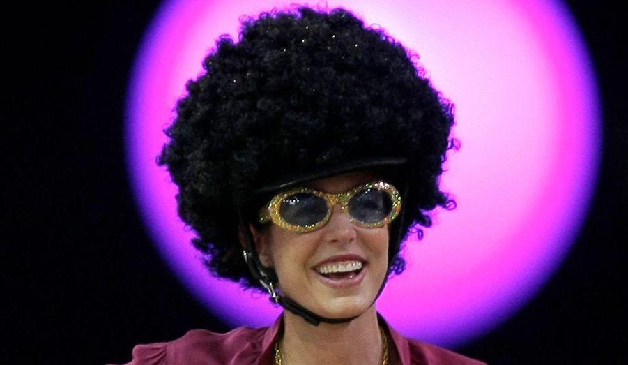 """Charlotte Casiraghi a participé à la 3ème édition des Gucci Masters ce week-end, à Villepinte. Marraine de l'épreuve Style et Compétition au profit de l'Amade, association caritative fondée par sa grand-mère Grace de Monaco, en faveur des enfants défavorisés, a revêtu pour l'occasion une perruque très """"Jackson Five"""" et des lunettes de soleil pailletées ou encore un collier """"Peace and love"""", pour un style tout droit sorti des années 70!"""
