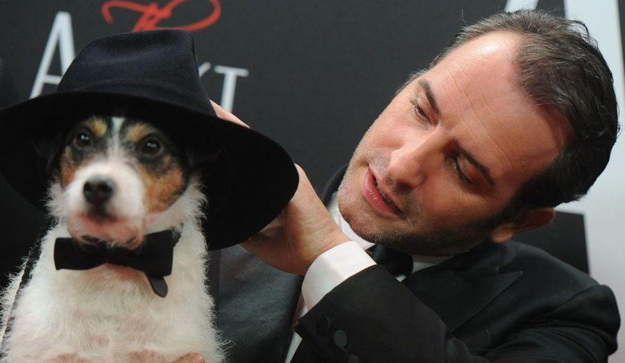 """L'acteur français Jean Dujardin pose avec son chien sur le tapis rouge du Palais du film Delphi à l'occasion de la première allemande du film """"The Artist"""" à Berlin, mardi."""