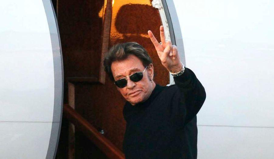 Johnny Hallyday salue ses fans avant de monter dans un jet privé à l'aéroport du Bourget, près de Paris.