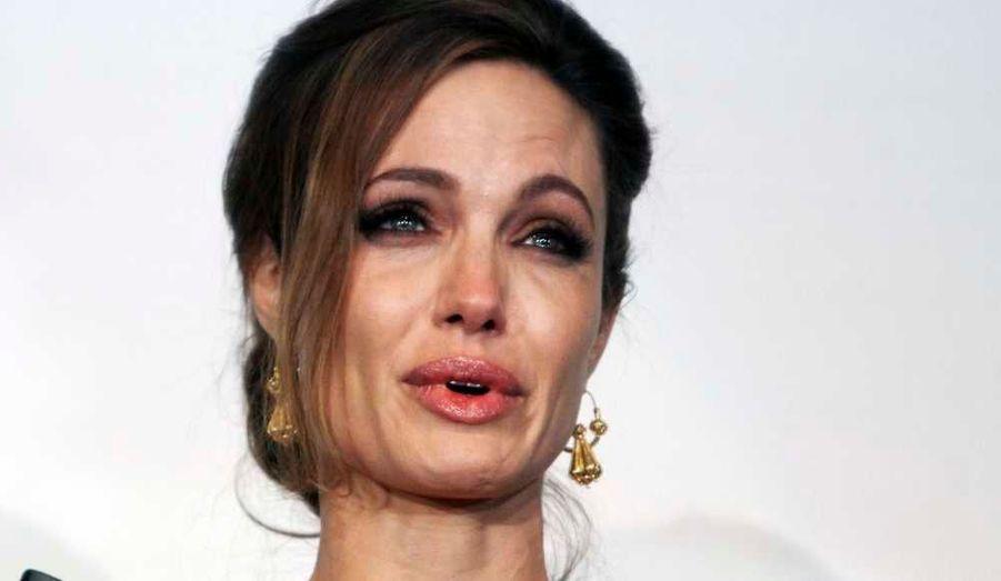 """Angelina Jolie et son compagnon Brad Pitt sont à Sarajevo, où a eu lieu hier soir la première de son premier film en tant que réalisatrice, Au pays du sang et du miel, qui a été projeté dans une salle de sport, devant quelque 5000 personnes. Accueillie par une standing ovation, la comédienne a fondu en larmes une fois sur scène. """"Vous voir accueillir (mon film) comme ça est extraordinaire pour moi. Je suis tellement reconnaissante envers tout le monde dans ce pays"""", a-t-elle ajouté. Et d'espérer qu'il servira d'exemple aux autorités sur l'attitude à avoir vis-à-vis de la répression sanglante en Syrie. """"Je crois que sa question centrale -qui est la nécessité d'une intervention et la nécessité pour le monde d'ouvrir les yeux sur les atrocités quand elles se produisent- est vraiment, vraiment d'actualité, surtout avec ce qu'il se passe en Syrie aujourd'hui""""."""