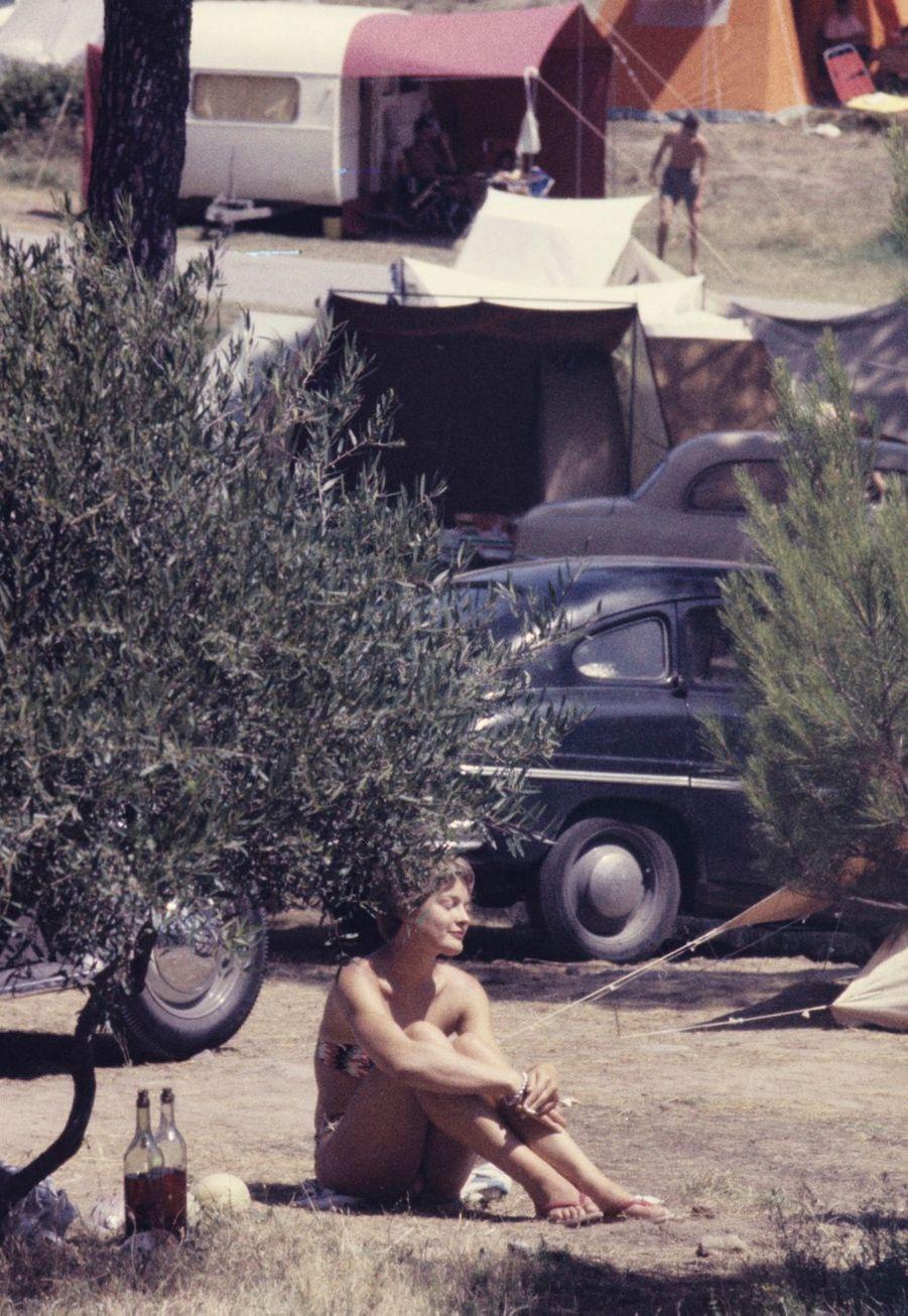 Côte d'Azur, 1958 : une jeune femme en bikini se prélasse dans un camp.