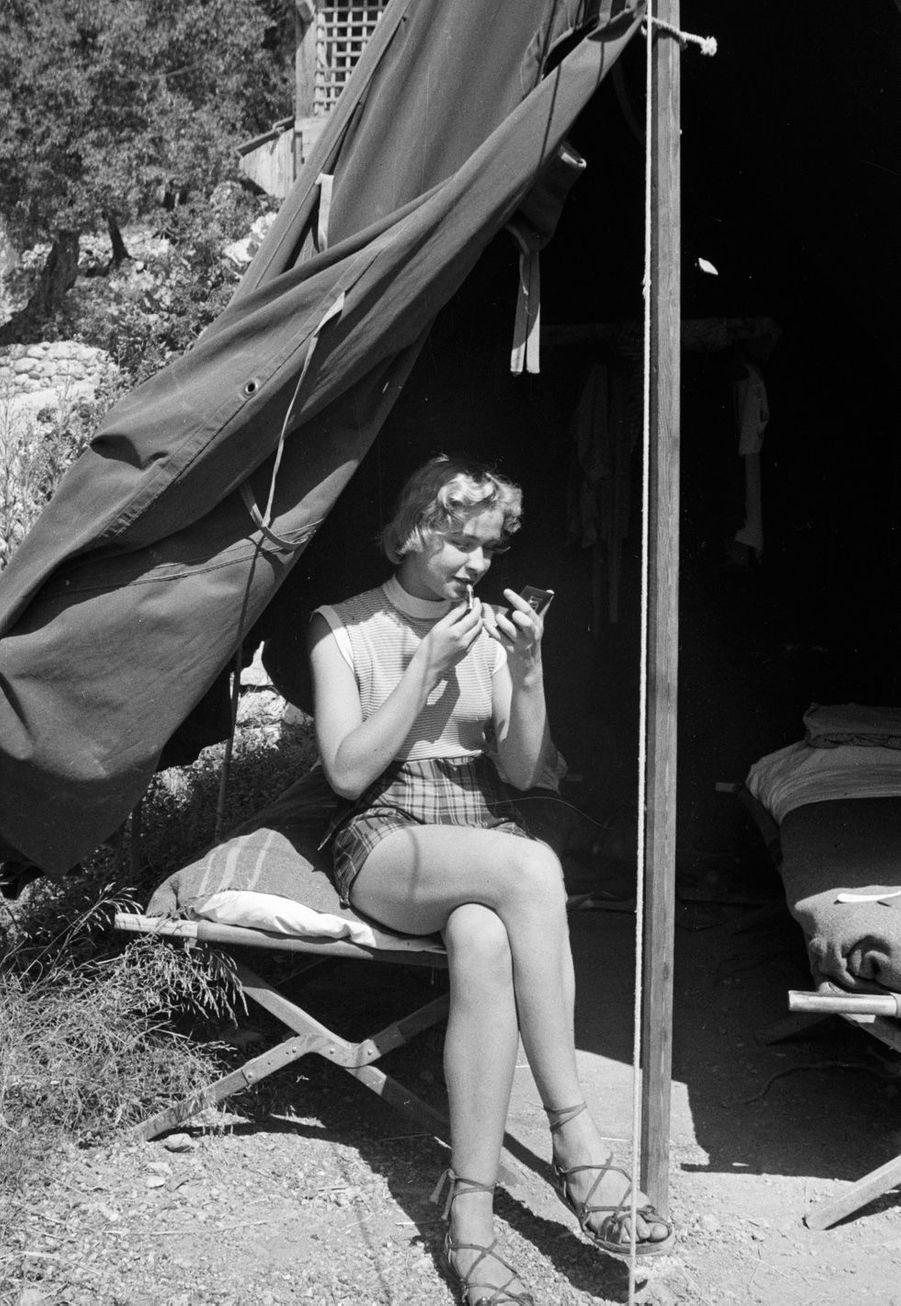 Côte d'Azur, 1955 : séance de maquillage à l'abri du soleil sous la tente.