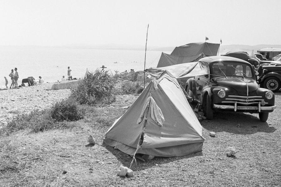 Côté d'Azur, 1958, camping sauvage : une tente plantée devant une voiture Renault.