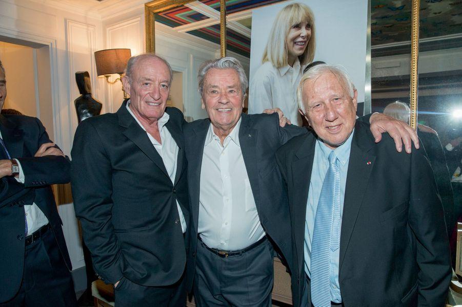Pascal Desprez, Alain Delon et Alain Deloche devant un portrait de Mireille sans lunettes.
