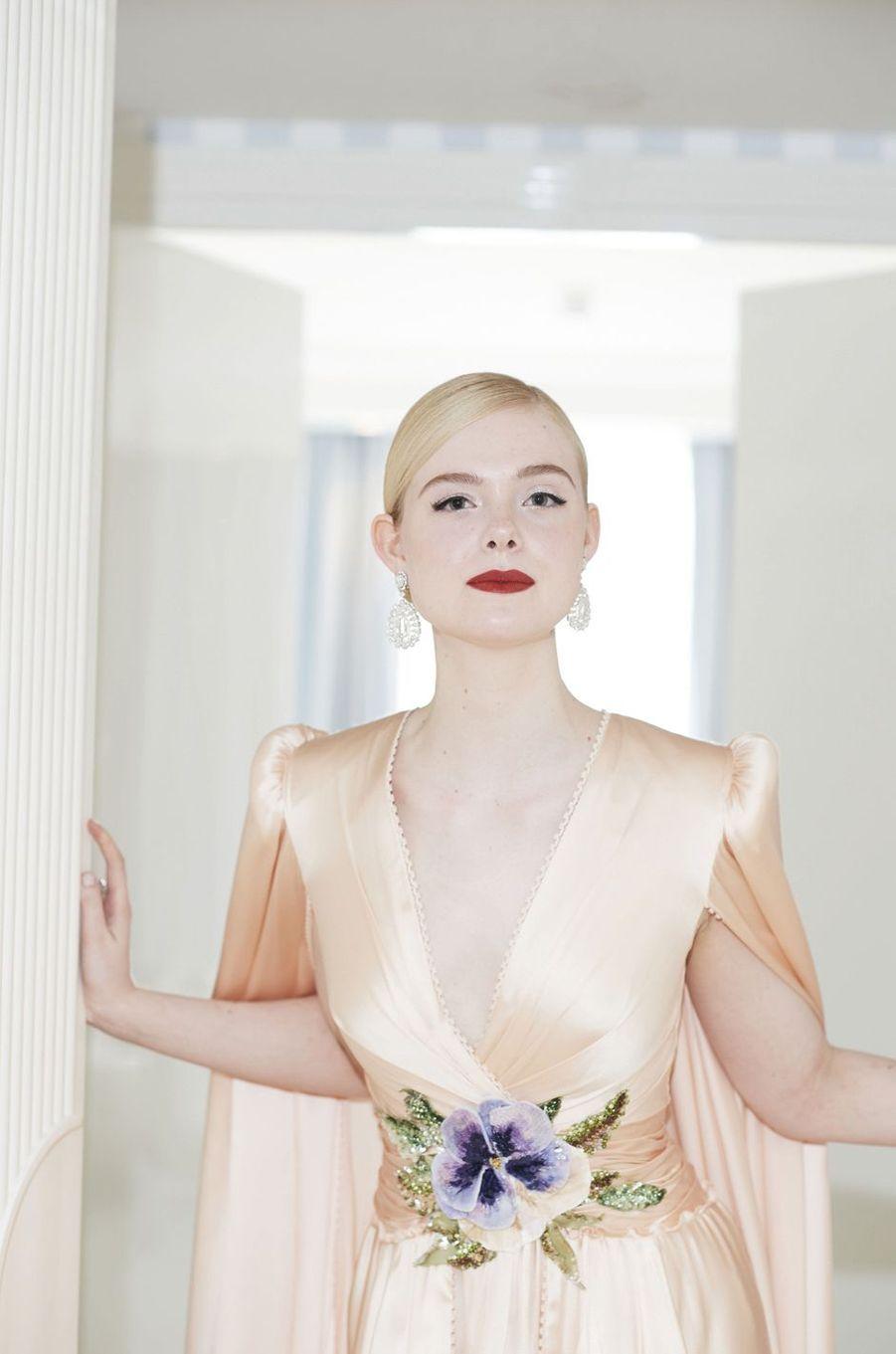 Dans une suite de l'hôtel Martinez. Elle Fanning, membre du jury, en princesse Aurore dans une robe Gucci qui semble avoir été créée pour mettre en valeur les précieux bijoux Chopard.
