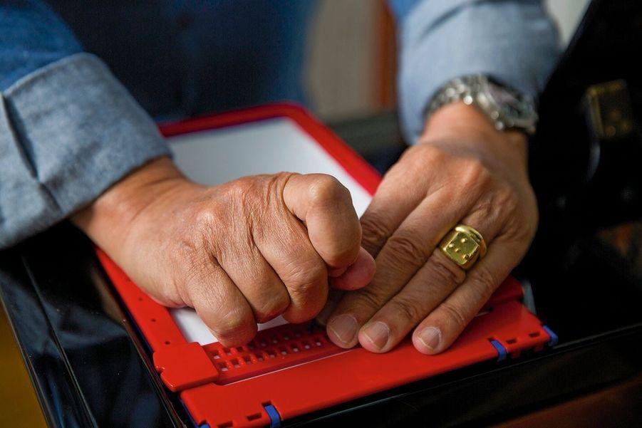 La tablette et le poinçon grâce auxquels Gilbert peut écrire, en braille, ses chansons.