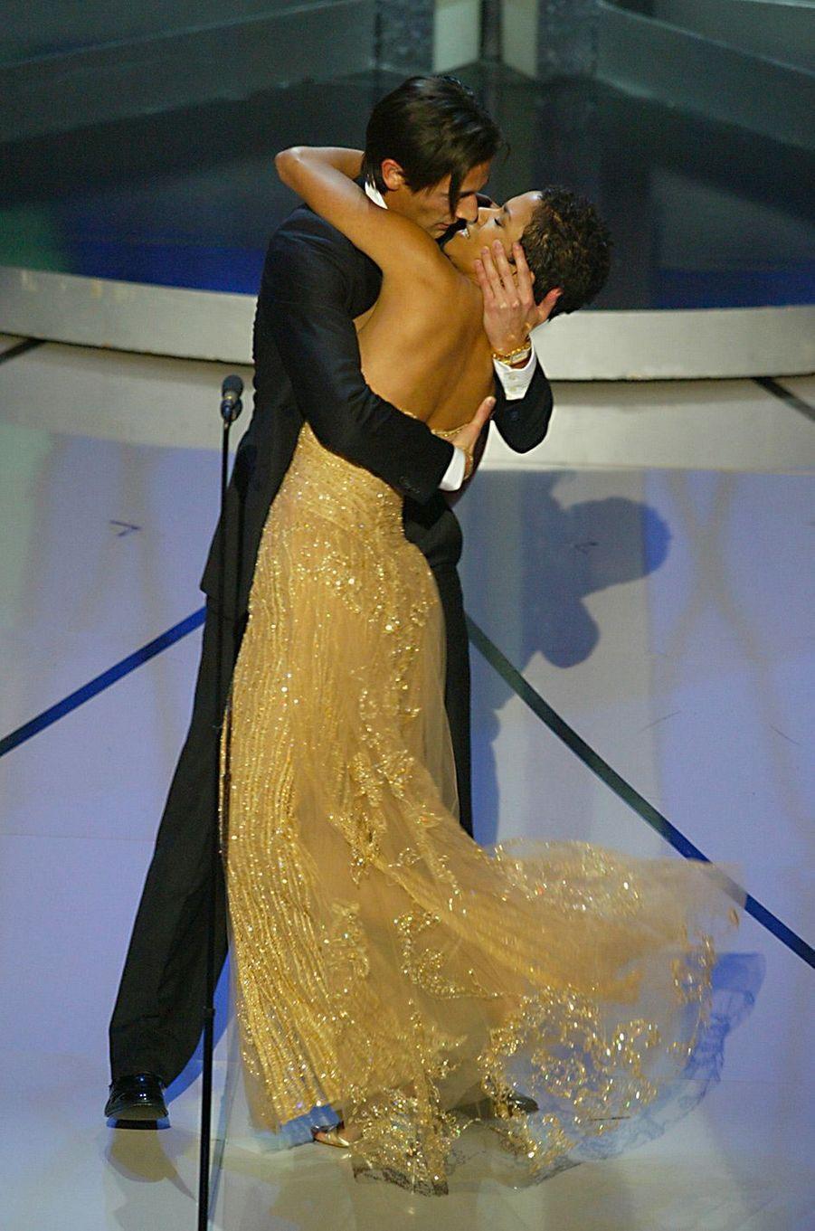 """75ème cérémonie des Oscars (2003)À 29 ans, Adrien Brody est le plus jeune acteur à remporter l'Oscar du meilleur acteur pour son rôle dans """"Le pianiste"""" de Roman Polanski. Sous le choc, il monte sur scène et... embrasse Halle Berry qui s'apprêtait à lui remettre la statuette. Plus tard, Halle Berry raconte qu'elle n'a pas compris ce qu'il se passait, mais s'est laissé faire, connaissant l'émotion incontrôlable que procure l'attribution d'un Oscar (elle a été sacrée meilleure actrice pour """"À l'ombre de la haine"""" en 2002).(Photo : Adrien Brody surprend Halle Berry en l'embrassant, 2003)"""