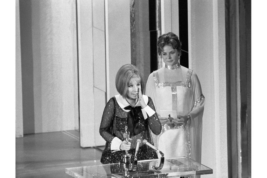 """41ème cérémonie des Oscars (1969)Surprise inédite : en ouvrant l'enveloppe, Ingrid Bergman n'a pu cacher sa stupéfaction... Deux comédiennes remportent ex-aequo l'Oscar de la meilleure actrice. Katharine Hepburn pour """"Le lion en hiver"""" et Barbra Streisand pour """"Funny Girl"""". Seule la deuxième montera sur scène pour faire un discours, Katharine Hepburn étant absente (comme à chaque cérémonie des Oscars).(Photo : Barbra Streisand fait son discours de remerciements sous les yeux d'Ingrid Bergman)"""