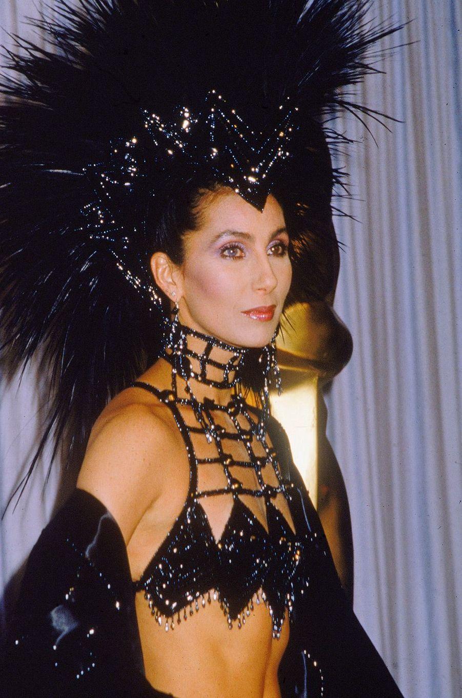 """58ème cérémonie des Oscars (1986)Plumes et paillettes. Alors qu'elle venait décerner l'Oscar du meilleur acteur dans un second rôle, Cher a fait sensation dans une tenue extravagante. """"Comme vous pouvez le voir, j'ai bien reçu la brochure de l'Academy expliquant comment s'habiller comme une actrice sérieuse"""", a-t-elle commenté avec humour.(Photo : Cher ne respecte pas vraiment le dress code aux Oscars de 1986)"""