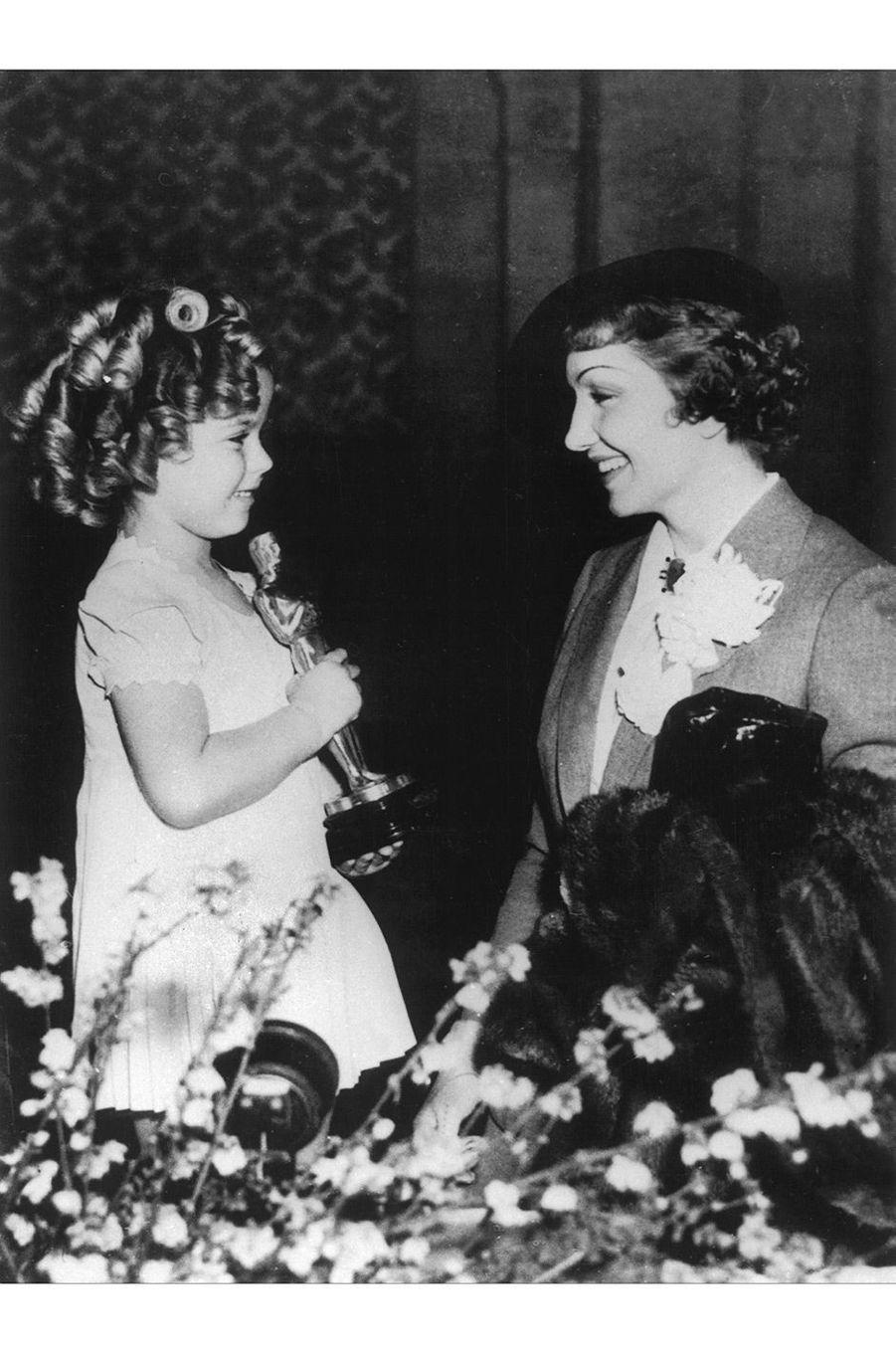 """7ème cérémonie des Oscars (1935)Claudette Colbert est la première française (naturalisée américaine) à remporter l'Oscar de la meilleure actrice pour son rôle dans """"New York-Miami"""" de Frank Capra(Photo : Claudette Colbert avec la jeune actrice Shirley Temple qui tient son Oscar en 1935)"""