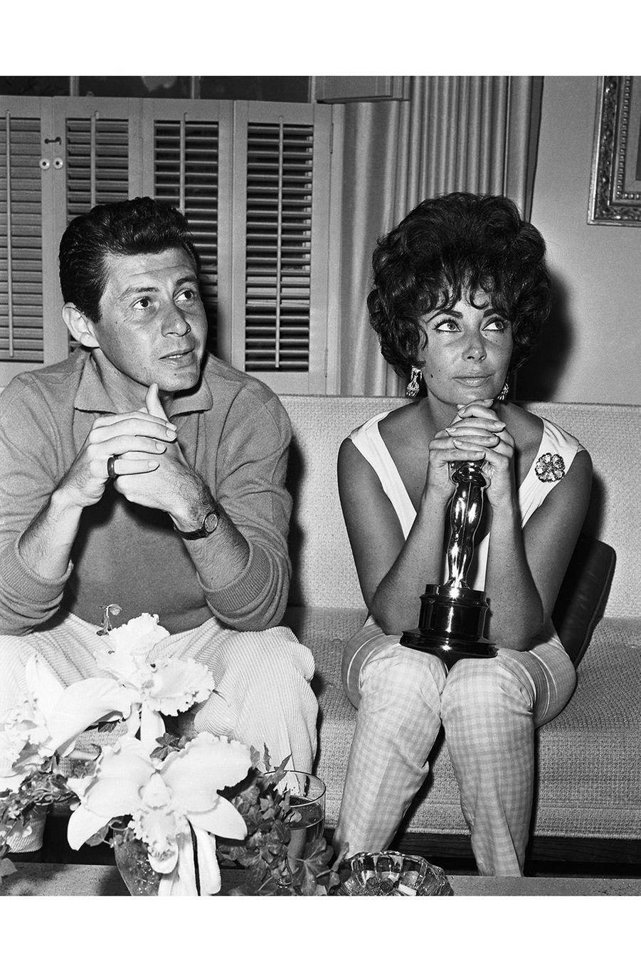 """33ème cérémonie des Oscars (1961)Elizabeth Taylor remporte son premier Oscar (elle en recevra trois au total) pour son rôle dans """"La Venus au vison"""", de Daniel Mann, sur fond de scandale : l'actrice a eu une liaison avec Eddie Fisher alors que celui-ci était marié à la populaire Debbie Reynolds. L'acteur a finalement divorcé pour épouser Elizabeth Taylor en 1959. Mais le public voit d'un mauvais oeil leur relation, et tique quand ils jouent ensemble dans """"La Venus au vison"""". Atteinte d'une pneumonie, Elizabeth Taylor regagne la sympathie des spectateurs. C'est le souffle court, toujours pas guérie de sa maladie, que l'actrice monte sur scène pour récupérer sa récompense.(Photo : Elizabeth Taylor reçoit l'Oscar de la meilleur actrice en 1961)"""