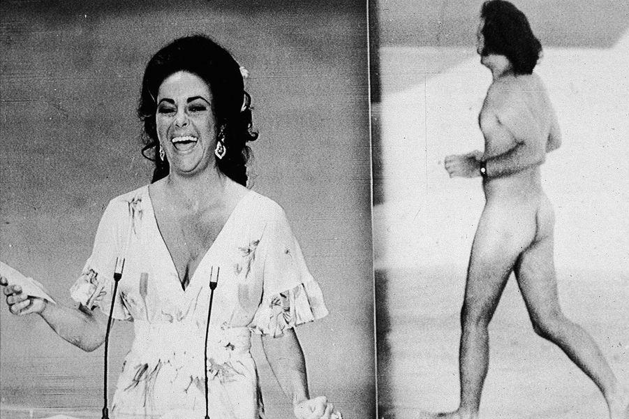 """46ème cérémonie des Oscars (1974)Irruption surprenante aux Oscars devant une salle remplie et 76 millions de téléspectateurs : le photographe Robert Opel traverse la scène entièrement nu alors que David Niven annonçait l'arrivée d'Elizabeth Taylor. Plus surprenant encore : le streaker n'a pas été arrêté, ni même exclu de la soirée. Lors d'une conférence de presse, il explique : """"Les gens ne devraient pas avoir honte d'être nus en public. En plus c'est un bon moyen de lancer une carrière"""".(Photo : Elizabeth Taylor prend à la rigolade l'irruption de Robert Opel sur la scène des Oscars en 1974)"""