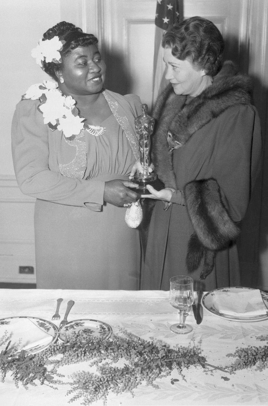 """12ème cérémonie des Oscars (1940)Hattie McDaniel est la première actrice noire à remporter un Oscar. Elle obtient l'award du meilleur second rôle féminin pour son jeu dans """"Autant en emporte le vent"""", de Victor Fleming, film qui bat le record de statuettes avec 10 récompenses(Photo : Hattie McDaniel reçoit l'Oscar des mains de Fay Bainter en 1940)"""