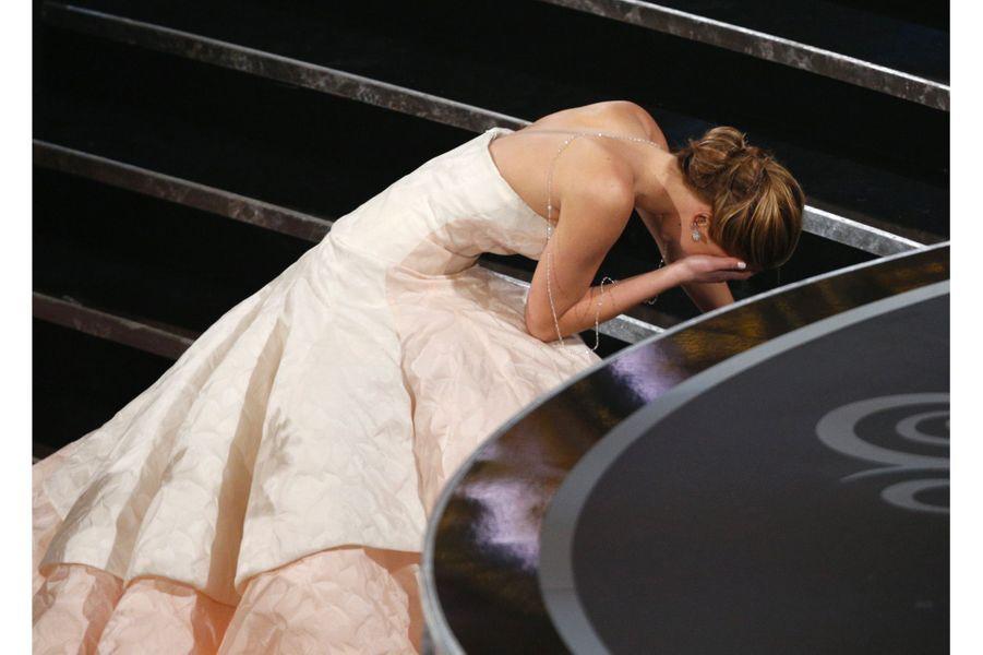 """85ème cérémonie des Oscars (2013)Et c'est la chute. Jennifer Lawrence, sacrée meilleure actrice pour son rôle dans """"Hapiness Therapy"""", de David O. Russell, se prend les pieds dans sa robe alors qu'elle monte sur scène. Aidée par Hugh Jackman, elle atteint finalement le pupitre sous une standing ovation, et plaisante : """"Vous êtes tous debout simplement parce que vous vous sentez mal que je sois tombée"""". Puis ajoute : """"C'est embarrassant...""""(Photo : Jennifer Lawrence à les jambes qui tremblent alors qu'elle reçoit l'Oscar de la meilleure actrice en 2013 ?)"""