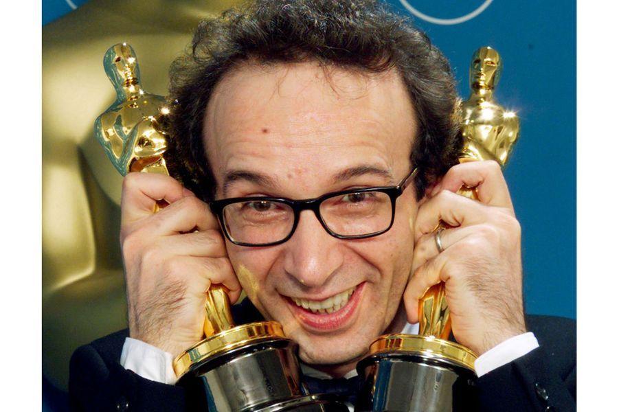 """71ème cérémonie des Oscars (1999)Incontrôlable : alors qu'il remporte l'Oscar du meilleur acteur pour """"La vie est belle"""", Roberto Benigni ne cache pas son euphorie. Il grimpe sur les sièges rouges duDorothy Chandler Pavilion (avec l'aide de Steven Spielberg) et lève le point haut, puis saute de sièges en sièges pour rejoindre l'allée qui l'amène à la scène. Son film remporte également le prix du meilleur film en langue étrangère.(Photo : Roberto Benigni pose avec ses deux statuettes en 1999)"""