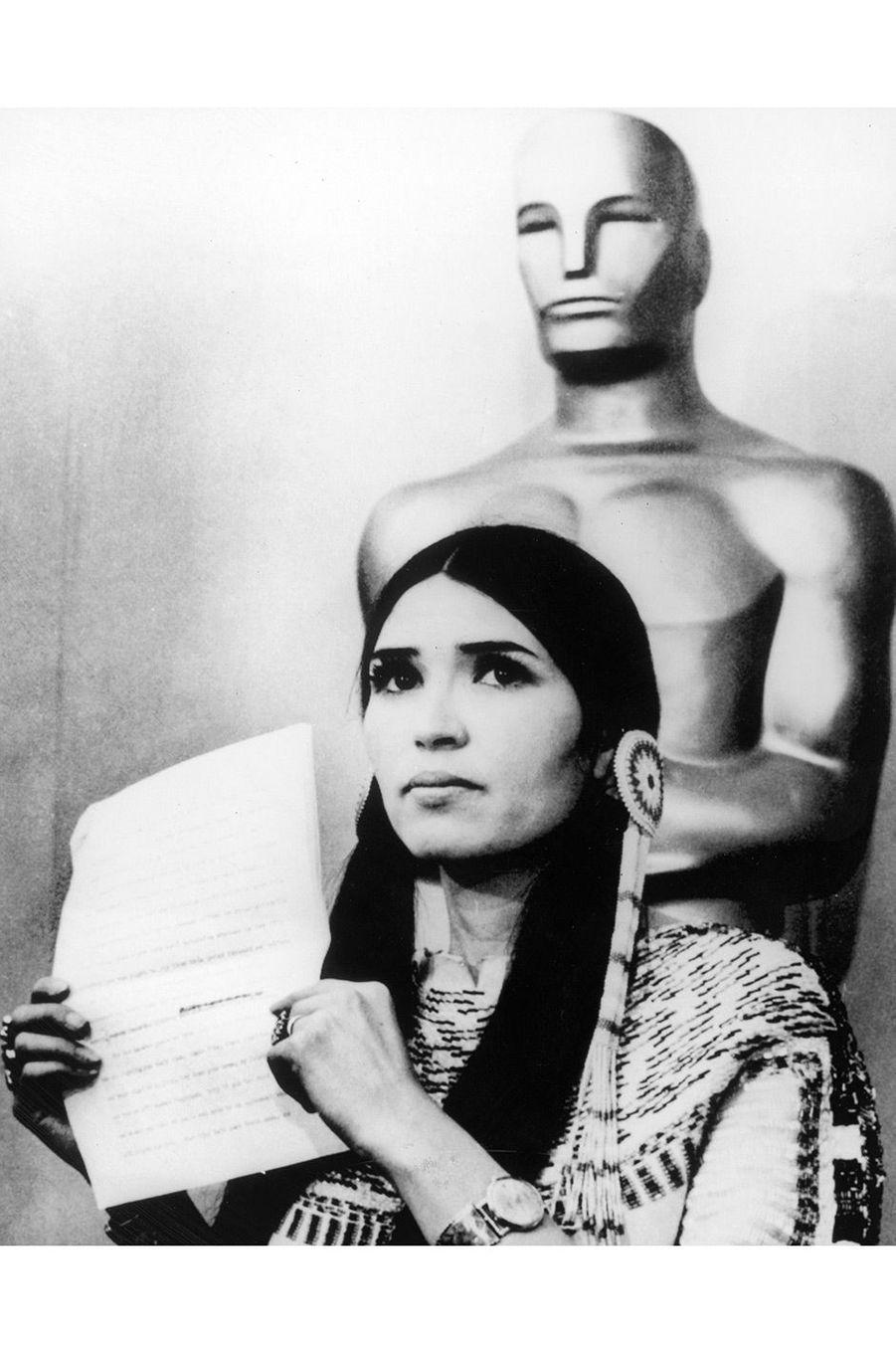 """45ème cérémonie des Oscars (1973)Quand l'Oscar du meilleur acteur est décerné à Marlon Brando pour son rôle dans """"Le Parrain"""", de Francis Ford Coppola, ce n'est pas le comédien qui se présente sur scène mais l'activiste Sacheen Littlefeather. """"Je représente Marlon Brando ce soir, et il m'a demandé de vous dire... qu'il regrette de ne pas pouvoir accepter cette généreuse récompense. La raison : le traitement des Indiens d'Amérique par l'industrie du cinéma"""". Plus tard, elle commentera ce moment ainsi : """"John Wayne était prêt à me faire sortir de scène à tout moment"""".(Photo : Sacheen Littlefeather brandit le discours qu'elle a fait sur la scène des Oscars à la place de Marlon Brando, en 1973)"""
