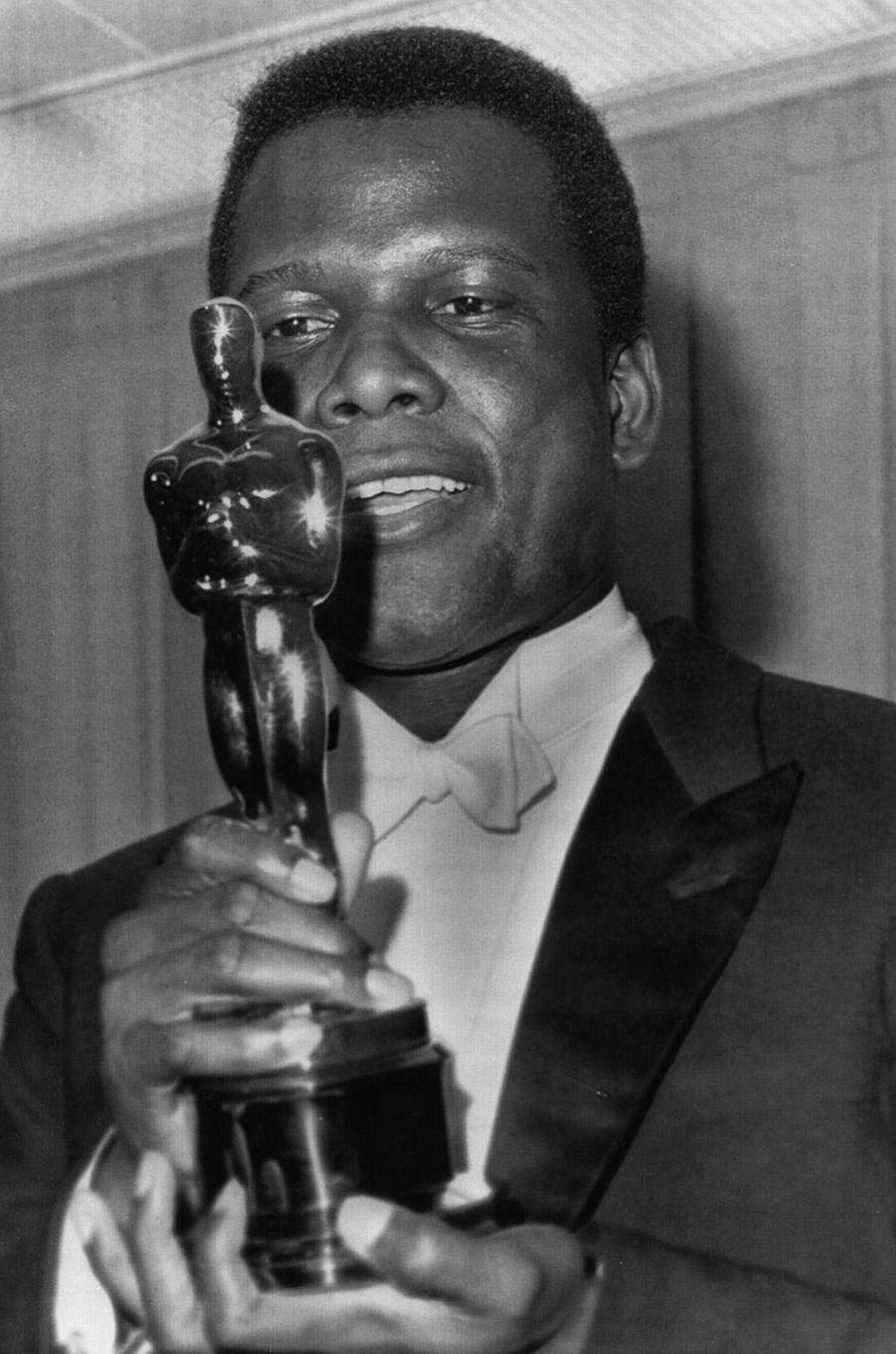 """36ème cérémonie des Oscars (1964)Sidney Poitier, pour son rôle dans """"Le Lys des Champs"""", de Ralph Nelson, est le premier comédien noir à recevoir l'Oscar du meilleur acteur. Ce n'est que 38 ans plus tard qu'un autre acteur noir recevra cette même récompense : Denzel Washington pour """"Training Day"""" en 2001.(Photo : Sidney Poitier admire son Oscar en 1964)"""
