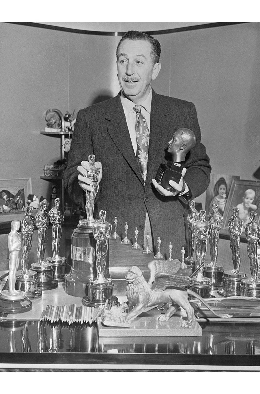 """6ème cérémonie des Oscars (1934)Walt Disney utilise pour la première fois le terme """"Oscars"""" qui deviendra le nom de cette cérémonie de récompenses, auparavant appelée """"Academy Awards"""" en référence à l'association """"Academy of Motion Picture Arts and Sciences"""" qui l'organise(Photo : Walt Disney pose avec tous ses trophées en 1954)"""