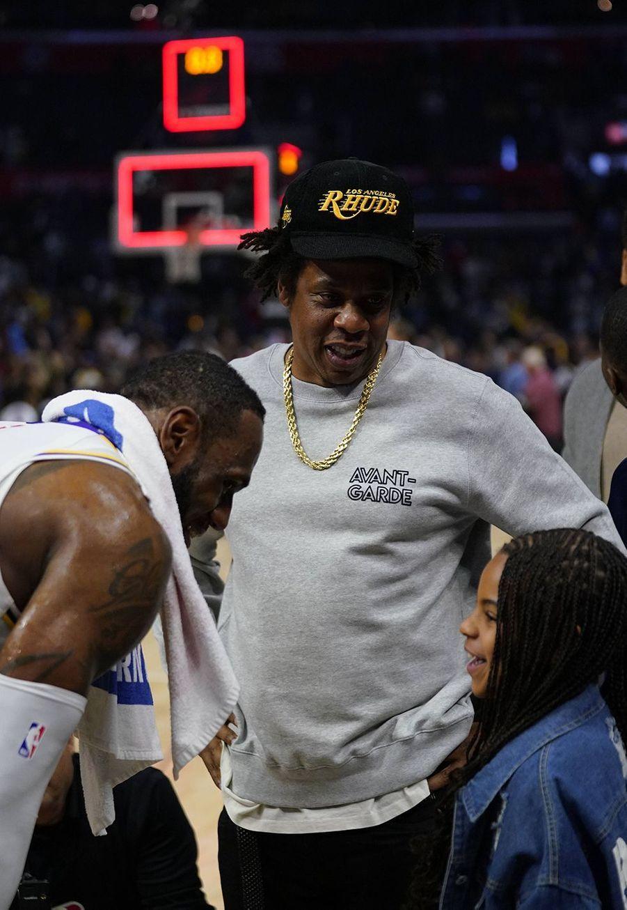 Jay-Z et sa fille Blue Ivy discutent avec LeBron Jameslors d'un match opposant les Lakers aux Clippers à Los Angeles le 8 mars 2020