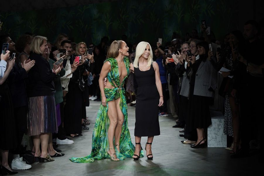 Jennifer Lopez dans sa Jungle Dress, faisant une apparition surprise à la fin du défilé Versace (ici avec Donatella)à la semaine de la mode à Milan, le 20 septembre 2019.