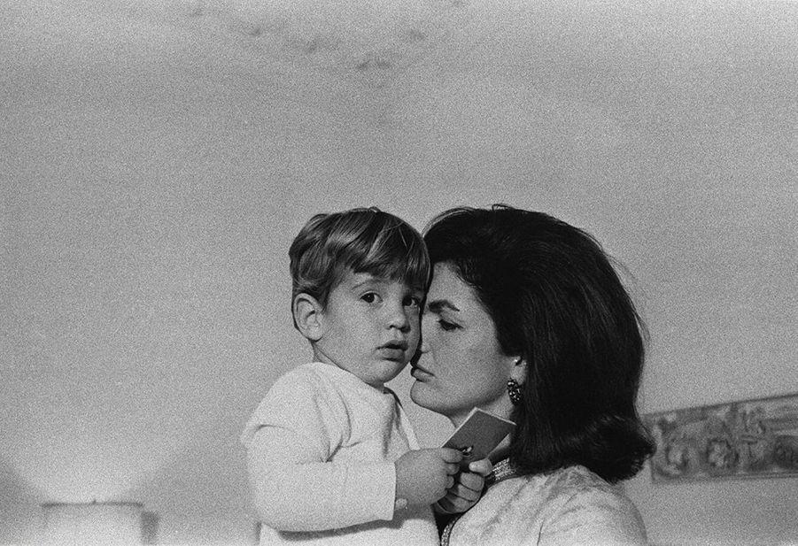 JohnJr. dans les bras de sa mère Jackie en 1963.