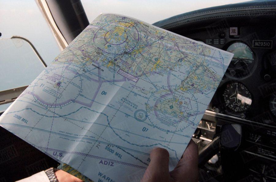 Un an après sa mort, Paris Match avait reconstitué le dernier jour de John John, le vendredi 16 juillet 1999 : ici, les mains du pilote aux commandes de l'avion Piper Saratoga II HP en vol, tenant une carte géographique indiquant l'île de Martha's Vineyard.