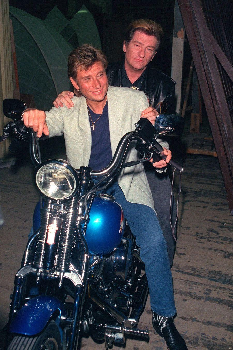"""Le chanteur Johnny Hallyday, accompagné de son ami Eddy Mitchell, pose sur la moto Harley Davidson qui lui a été offerte pour son 46è anniversaire dans le cadre de l'émission """"Sacrée Soirée"""" de Jean-Pierre Foucault dont il était l'invité, le 14 juin 1989."""