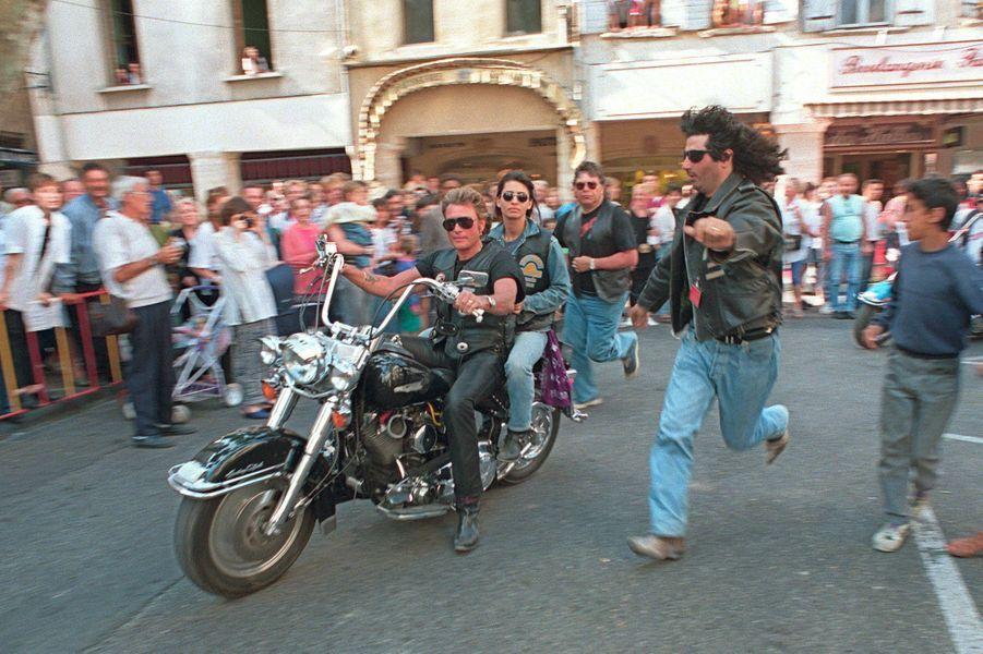 Le chanteur de rock et acteur français, Johnny Hallyday, arrive le 04 juin 1994 avec sa femme Adeline, au guidon d'une Harley-Davidson, devant la mairie de Capentras.