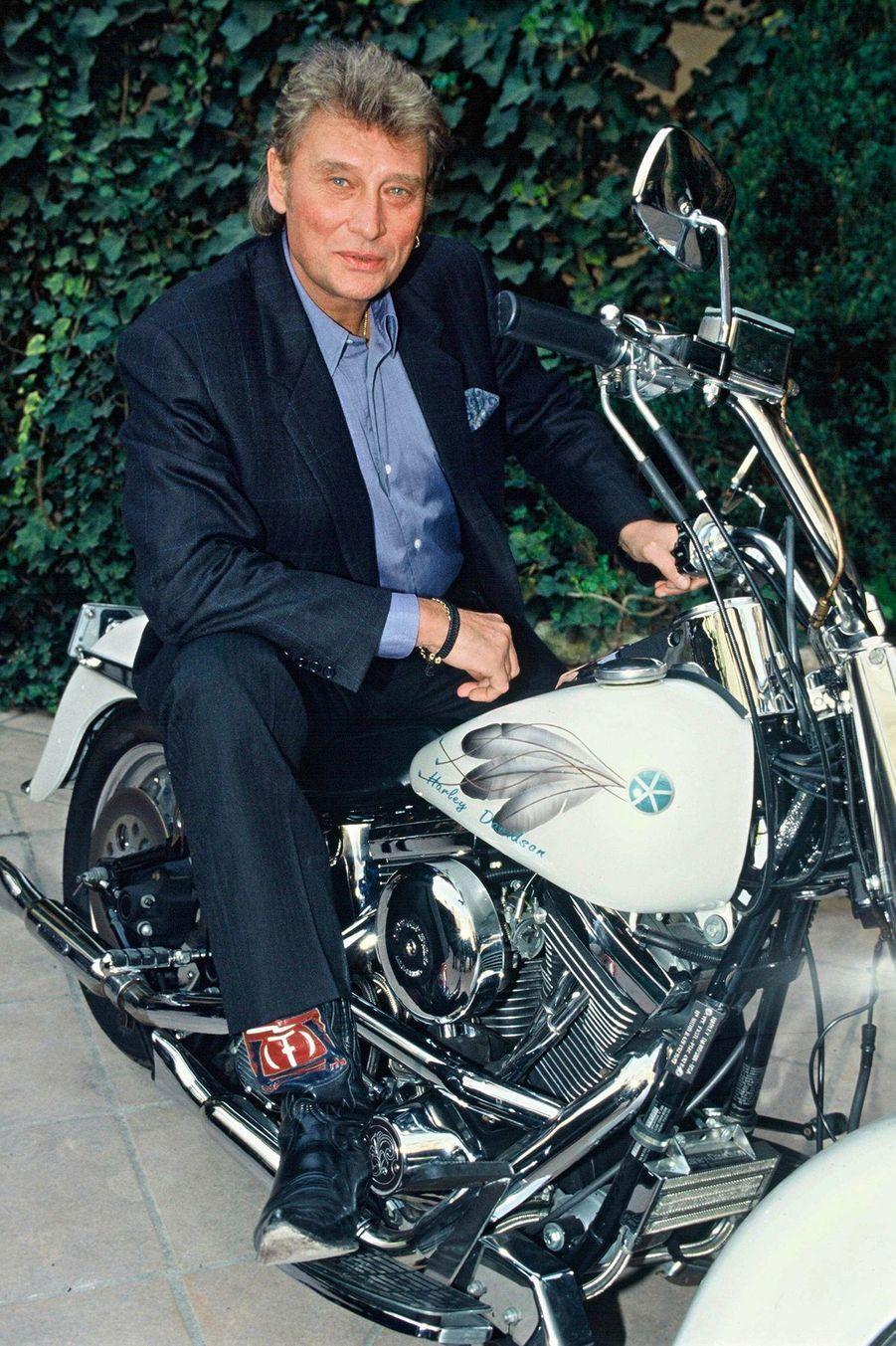 Johnny Hallyday posant sur une Harley Davidson en 1992.